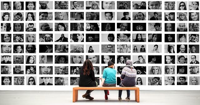 lidé před fotkami lidí
